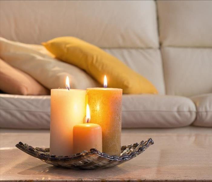 lit candles on a marble table and in the background a sofa with pillows